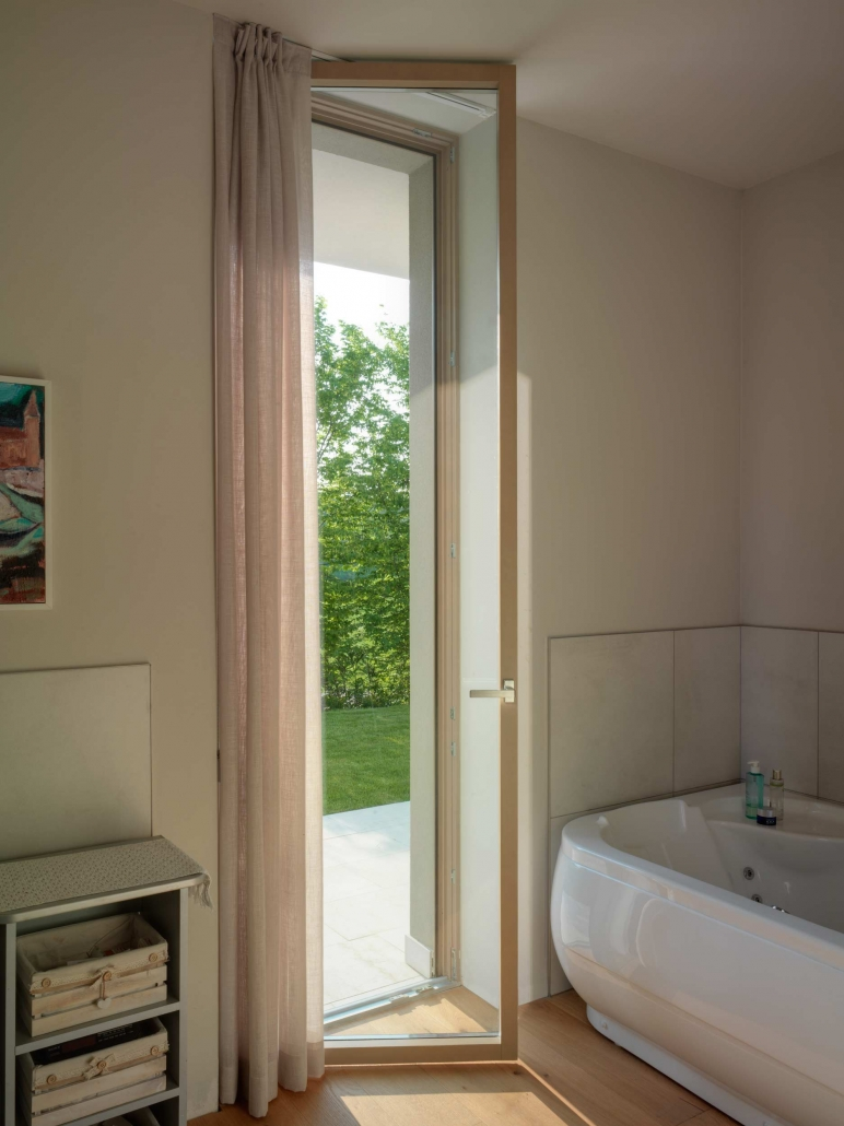 A custom floor to ceiling minimal frame inswing wood door