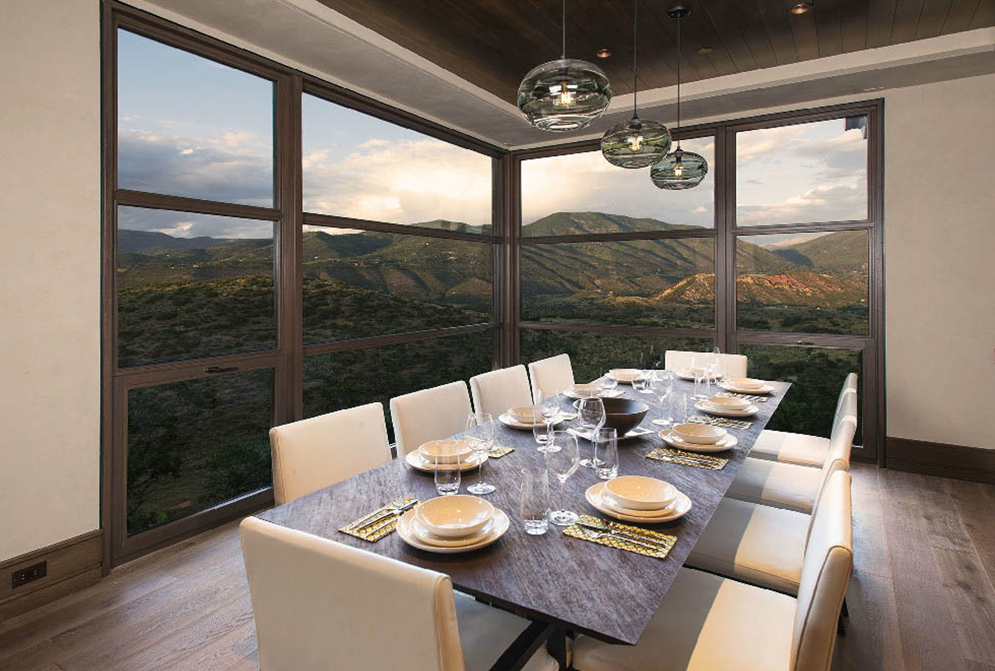 A dining room with a view through custom wood windows by Veranda View.